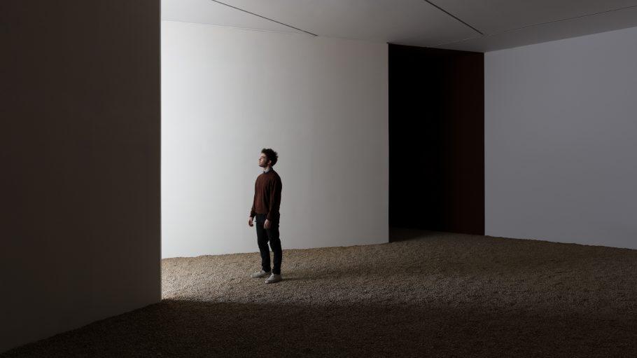 Ein Mann steht in einem weißen Raum auf Sand