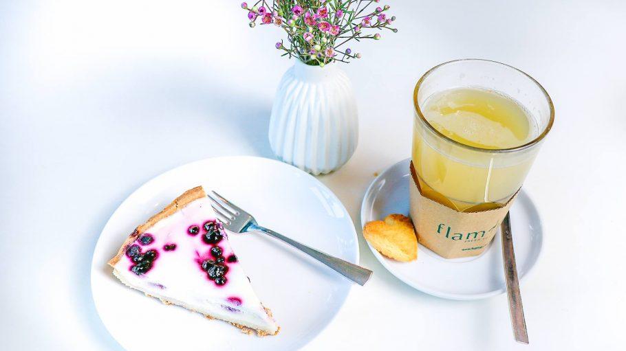 Kuchen auf Teller neben Tee und schönen Blumen in Vase