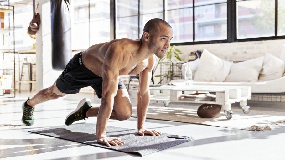 Junger Mann mit nacktem Oberkörper macht Fitness in Loft