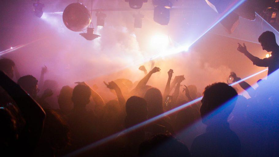 Tanzende Menschen als Silhouetten in Club, weißes Licht