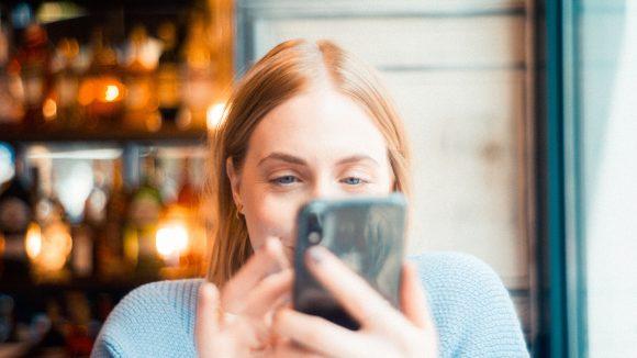 Frau mit Handy allein am Tisch