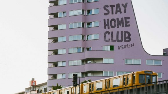 """Lila Hochhaus mit Aufschrift """"Stay Home Club Berlin"""", davor orange U-Bahn auf Hochbahntrasse"""