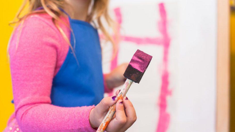 Mädchen mit Malerpinsel mit pinker Farbe