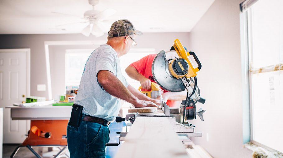 Handwerker sägen Holzbretter im Wohnzimmer