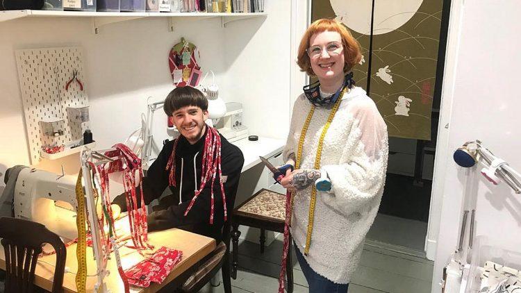 Frau mit roten Haaren und Brille und Mann mit dunkler Topffrisur in Atelier mit Nähmaschine