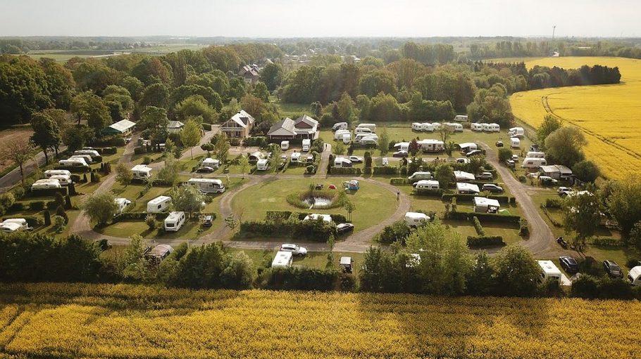 Drohnenbild von Campingplatz mit Wohnmobilen zwischen Rapsfeldern und Bäumen