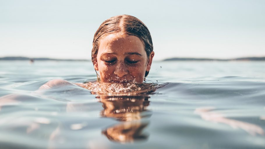 Frau badet in einem See.