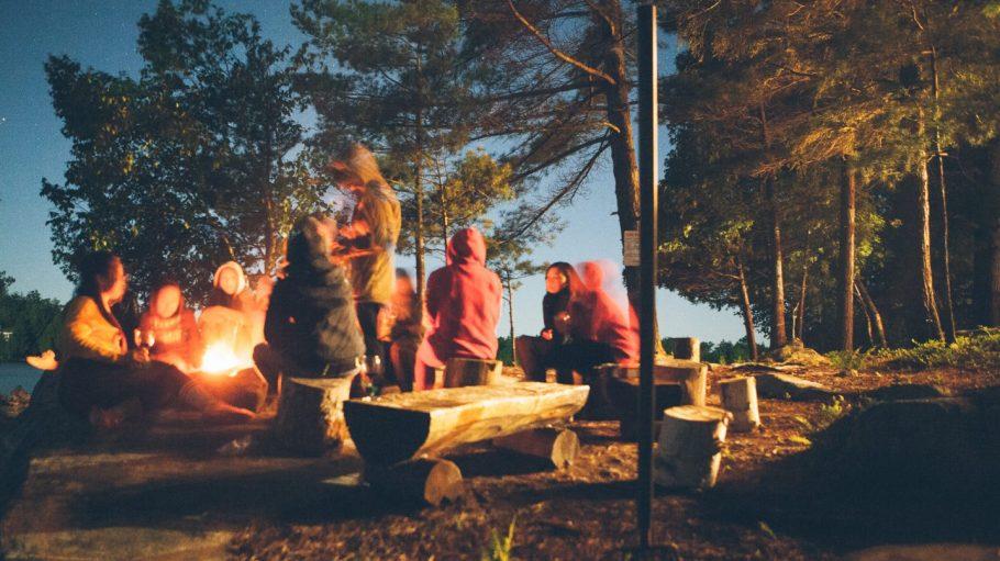 Menschen sitzen an Feuer auf Holzbänken im Wald