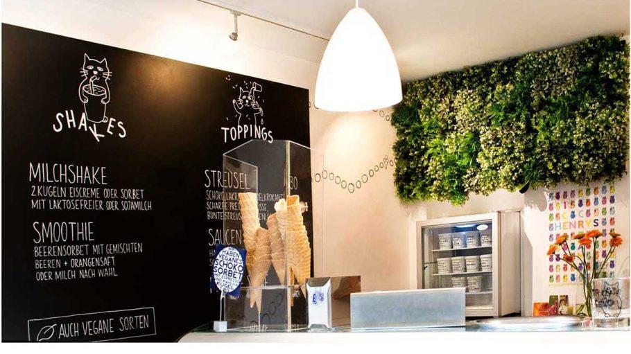 Laden mit weißen Lampen, grünen Pflanzen an Wand, Eistüten und schwarzer Tafel