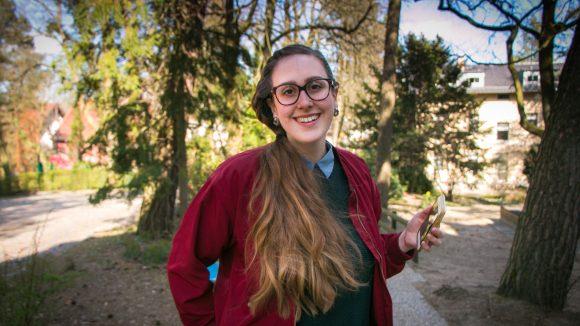 Frau mit grünem Pullover, weinroter Jacke und braunem, langen Haar und Brille
