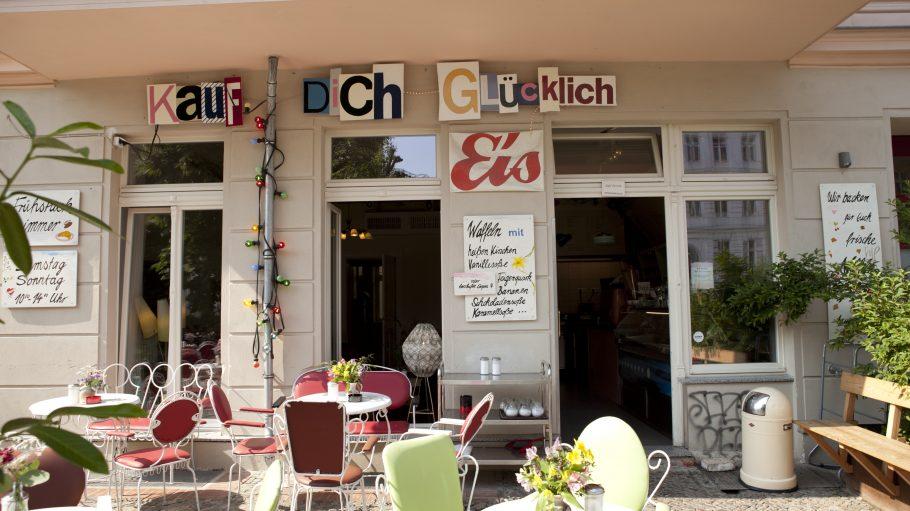 Café Kauf dich Glücklich von außen mit Stühlen auf der Terrasse