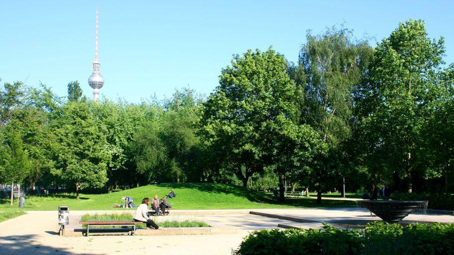 Park mit Menschen, Bank und Fernsehturm im Hintergrund