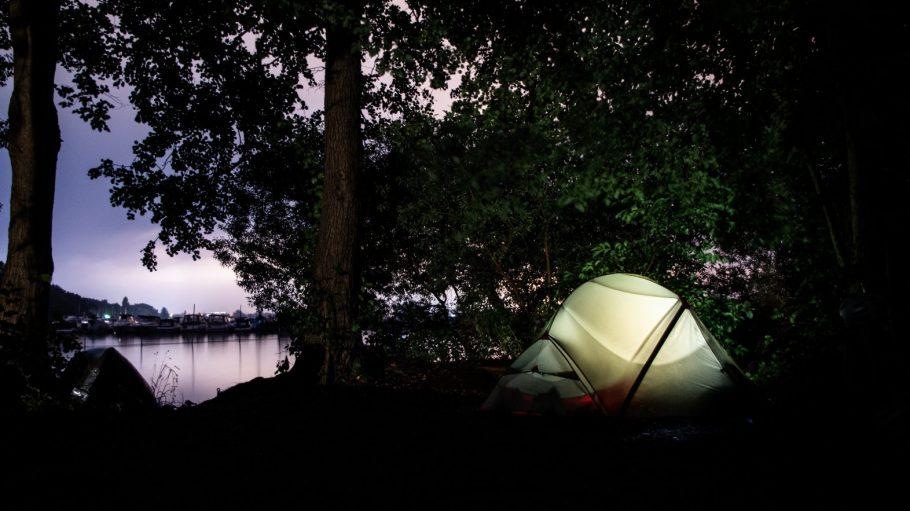 Weißes Zelt unter Baum am See