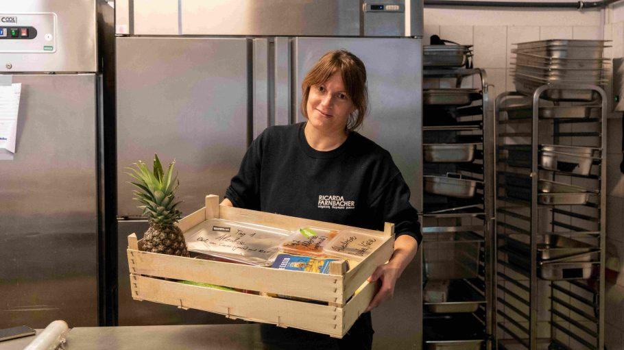 Frau mit Holzkiste und Essen in der Hand