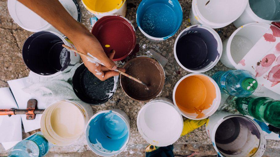Verschiedene Farbeimer mit Hand und Pinsel im Bild