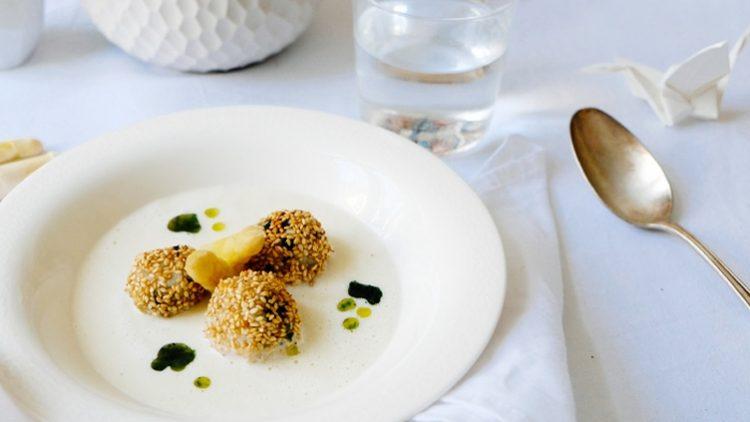 Drei Sesambällchen mit Spargel auf weißem Teller