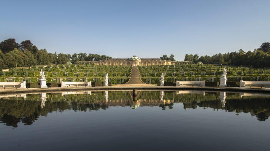 Schloss Sanssouci mit begrünten Terrassen, Marmorstatuen und Wasser davor