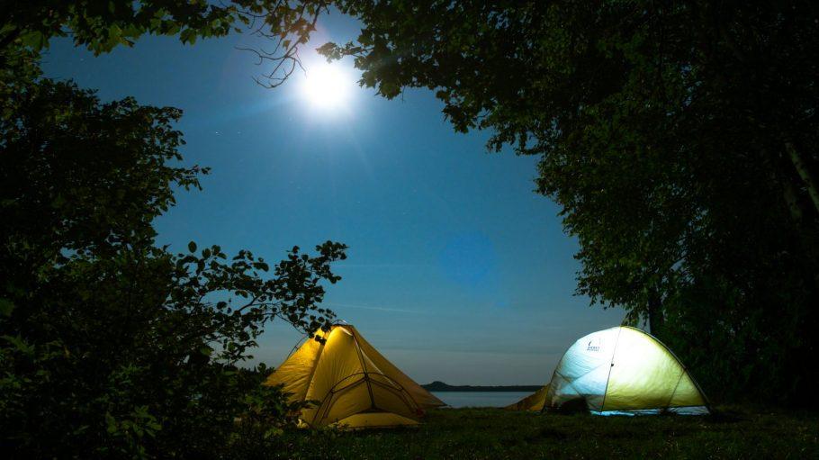 Gelbes und weißes Zelt am See unter Bäumen, Mond