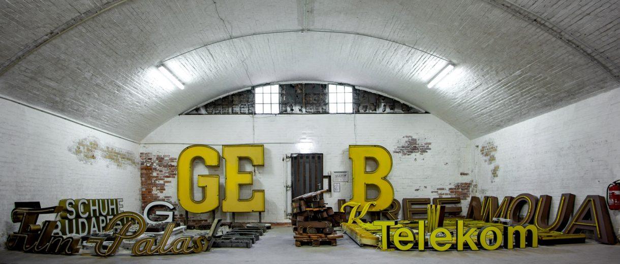 Lagerhalle weißgekalkt mit gelben Buchstaben