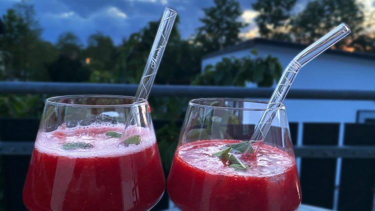 Erdbeersmoothies mit Glashalm auf Tisch
