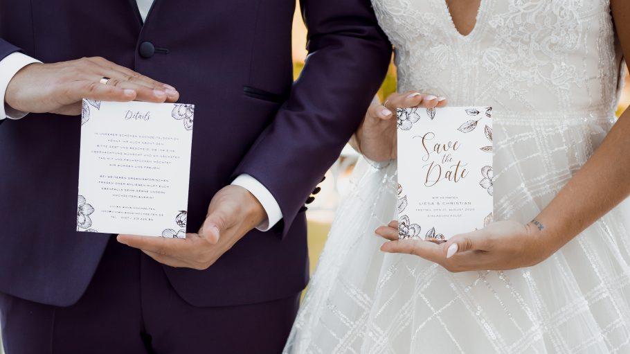 Hochzeitspaar mit Save the Date-Karten in der Hand