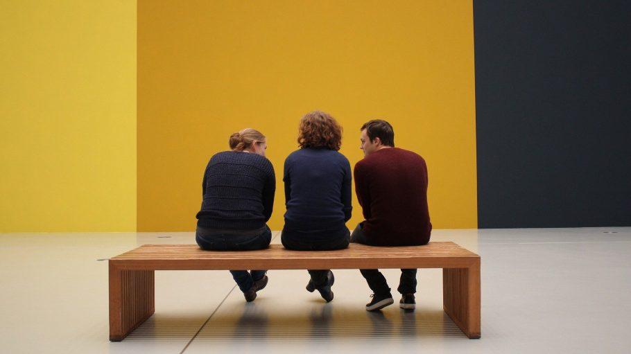 Zwei junge Frauen und ein Mann auf Bank in Museum blicken auf gelbe Wand