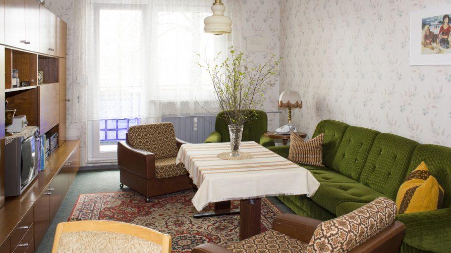 DDR-Wohnzimmer mit Tisch, Schrankwand, grünes Sofa