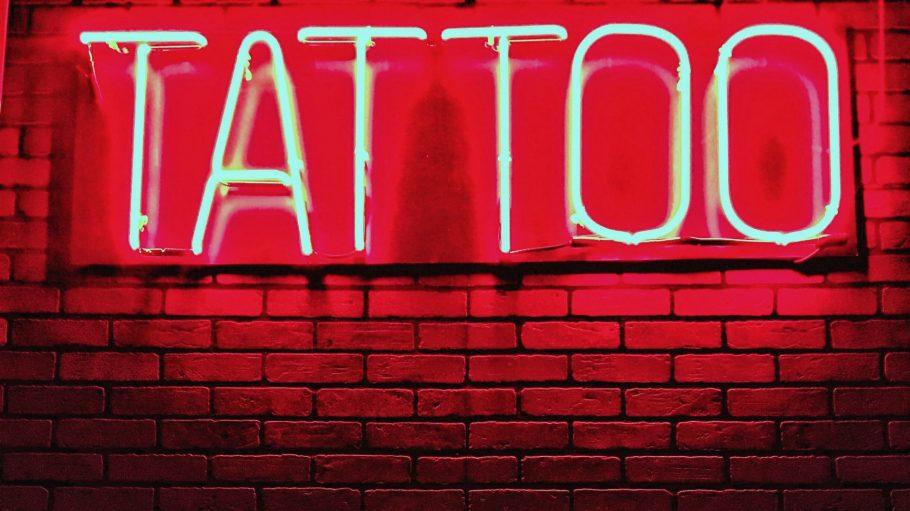 """Rötliche Leuchtreklame """"Tattoo"""" an Backsteinwand"""