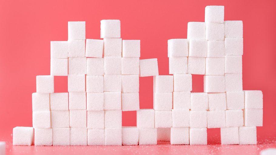 aufeinandergestapelte Zuckerstücke vor rosa Hintergrund