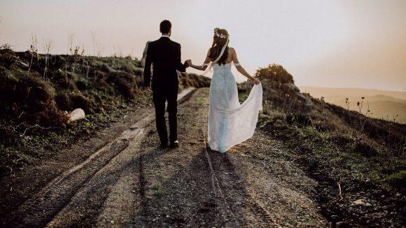 Hochzeitspaar von hinten auf Weg in der Natur