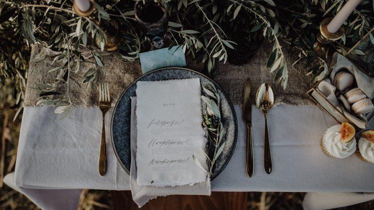 Gedeck mit Pflanzen-Deko und goldenem Besteck