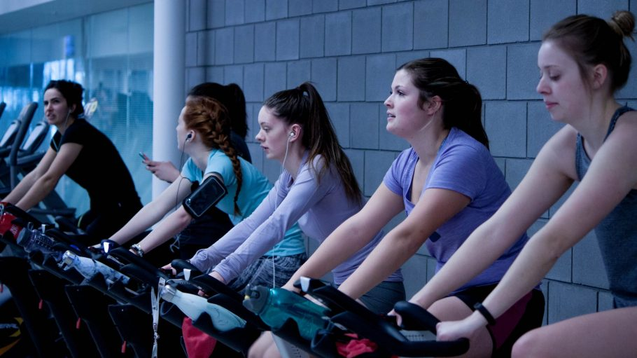women taking exercise on black stationary bikes in front of gray concrete wall