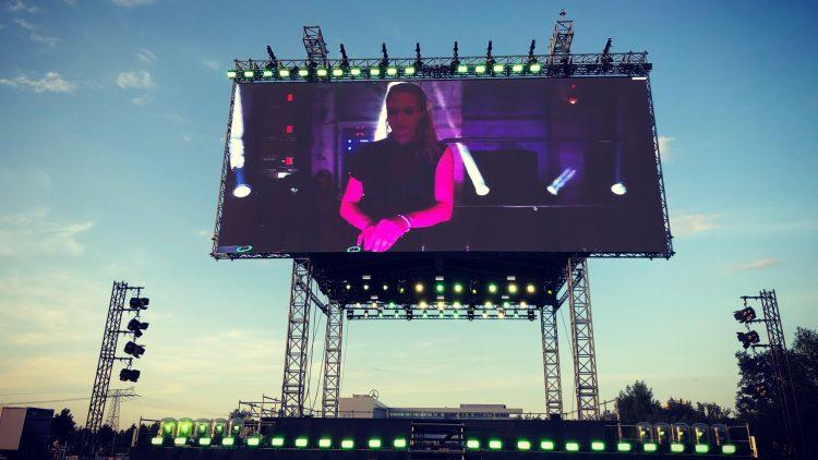 Große Leinwand, mit Stahlträgern befestigt, darauf weiblicher DJ