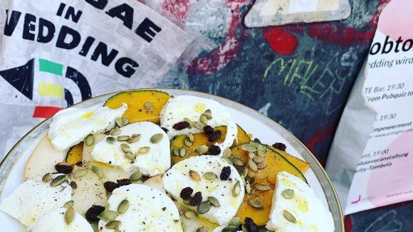 Teller mit Mozzarella, Gemüsescheiben und Kernen, dahinter Wand mit Tags und Plakaten