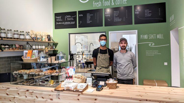 Zwei Männer, einer mit Mundschutz, hinter Tresen von Café