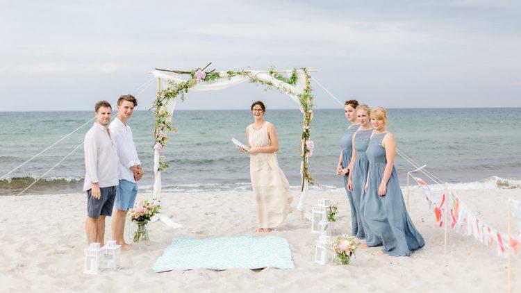 Spalier bei Hochzeit an Strand, links zwei junge Männer, rechts drei junge Frauen, unter grünem Bogen Hochzeitsplanerin Isabel Merfort