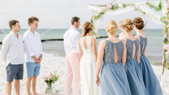 Hochzeitspaar, zwei Männer und drei Frauen in lockeren Klamotten am Ostseestrand