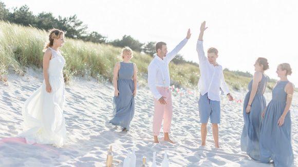 Zwei Männer und vier Frauen einer Hochzeitsgesellschaft am Strand