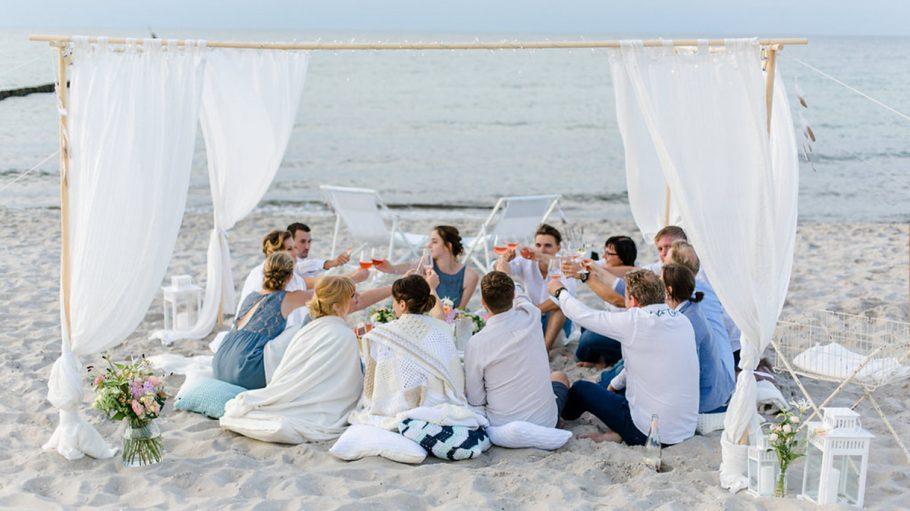Zwölf Hochzeitsgäste sitzen auf Sandstrand und prosten sich zu