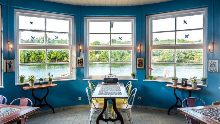 Runder Raum in Café mit Blick durch mehrere Fenster auf See
