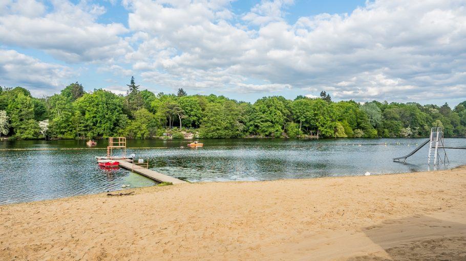 Strand und See, Steg, im Hintergrund Wald und blauer Himmel mit Wolken