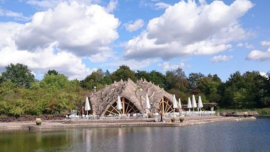 Restaurant an See von außen, Form eines Maulwurfshügels, davor Terrasse und See, dahinter Bäume