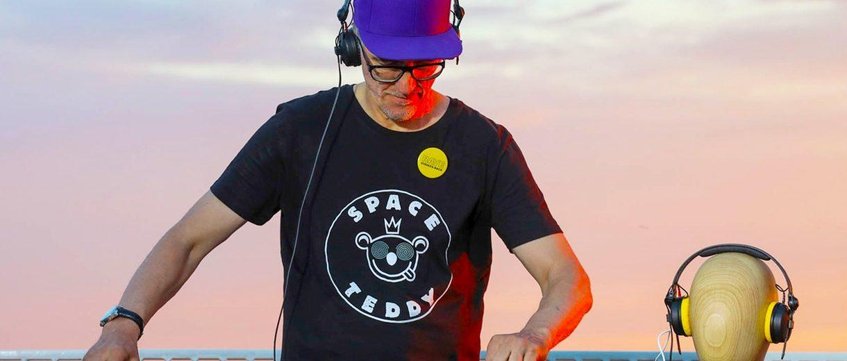 DJ Dr.Motte mit schwarzem T-Shirt mit weißem Aufdruck, Brille und blauer Basecap an DJ-Pult
