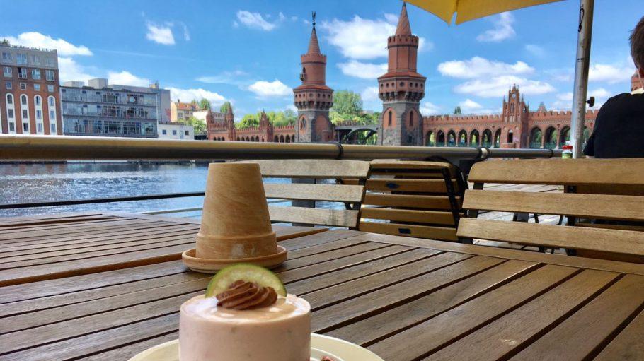 Holztisch auf Café-Terrasse mit Stühlen und Dessert, im Hintergrund Fluss Spree und Oberbaumbrücke in Berlin