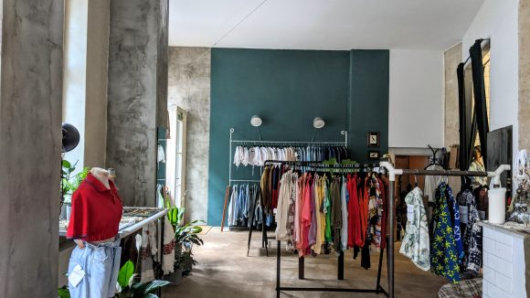 Kleidung auf Kleiderstangen im Laden.