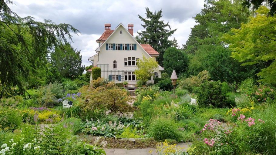 Karl-Foerster-Garten mit Pflanzen und Blumen, im Hintergrund weißes Landhaus, Bäume
