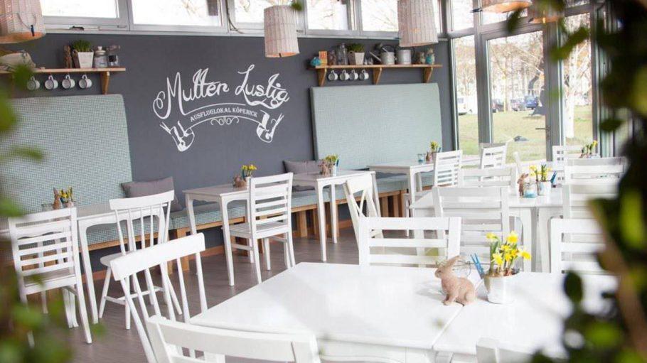 Ausflugslokal Mutter Lustig Innenraum mit weißen Tischen, großen Fenstern, Blümchen auf den Tischen