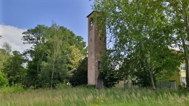Steinturm von Ludwig Persius steht auf Wiese in Potsdam-Bornim, zwischen Bäumen, rechts ein Haus