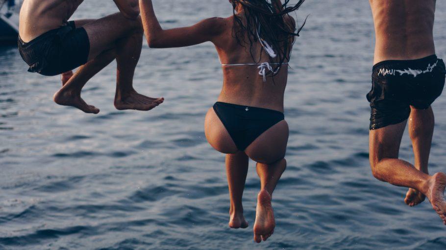 Zwei Männer und eine Frau in der Mitte springen ins Wasser