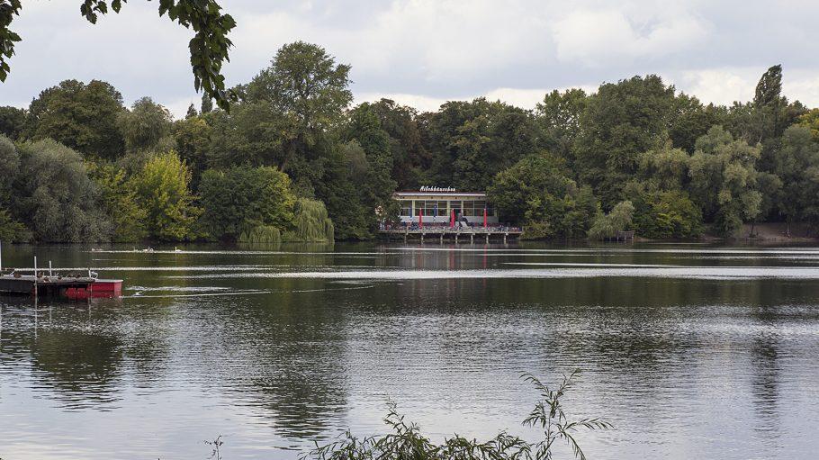 Weißer See mit Booten und Ast im Wasser, im Hintergrund Wald am Ufer und Gaststätte Milchhäuschen